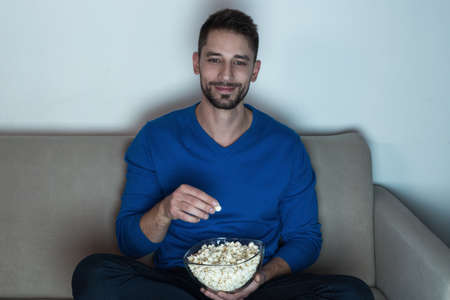 eating popcorn: Man eating popcorn, watching television