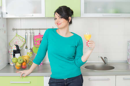 Woman holding juice in a kitchen Stock Photo