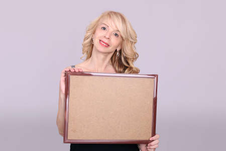 Blond lady showing  a board Stock Photo