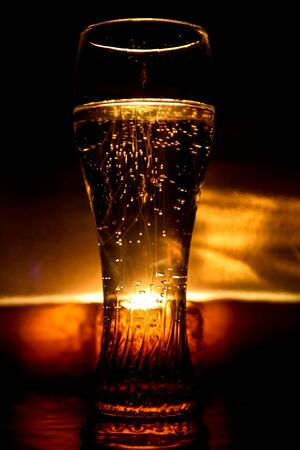 Big glass full with mineral water highlighted with a candle light behind Stock Photo