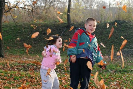little boy and girl playing with autumn leaves in the park Stock Photo