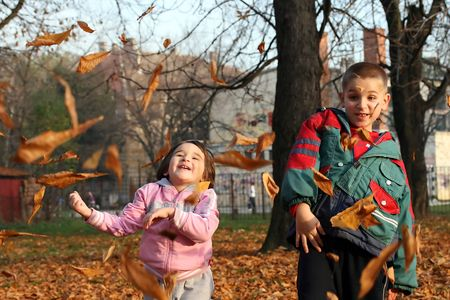 little boy and girl playing with autumn leaves in the park Stock Photo - 5981979