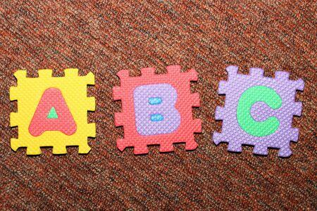 Buchstaben a, b, C, auf den Teppich aus farbigen Buchstaben-Puzzle.