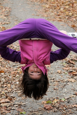 Little girl hanging upside down over the old metal pipes photo