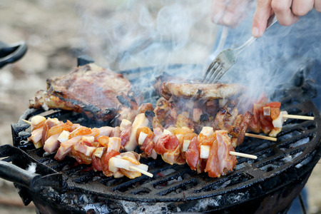 Nahaufnahme schoss von Spie� und Schweinefleisch auf dem Grill
