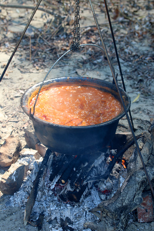 Cooking goulash in a pot on the fire.