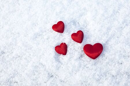 Red hearts on the snow