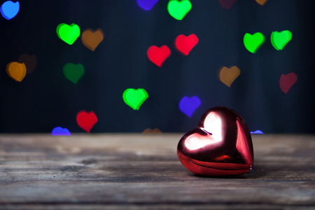 Red heart on the wooden table with a small hearts on a background Stock Photo