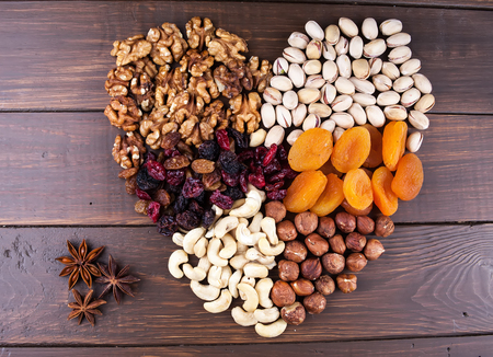Different kinds of nuts and dry fruits on the wooden table Stock Photo