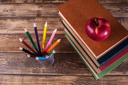 Books on the wooden table, red apple, colored pencils in glass Banque d'images