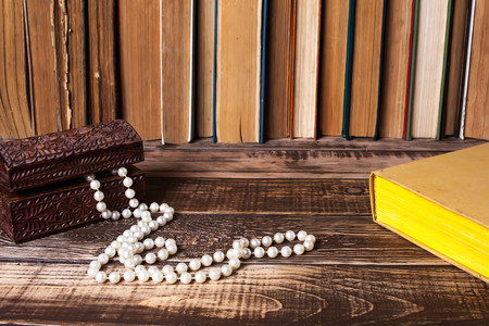Books on the wooden table, bead in casket on the book Stock Photo