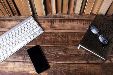 Books on the wooden table, notebook, white keyboard, phone, glasses