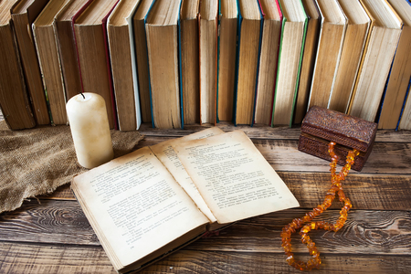 old styled: Old books with pen on the wooden table, white candle, casket with chapled, many books on background