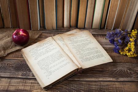 Oude boeken met pen op de houten tafel, rode appel, droge bloemen, veel boeken over de achtergrond