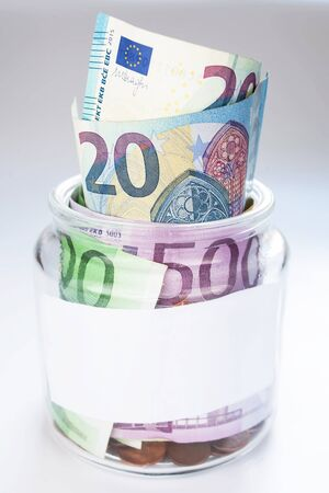 A jar with money and coins on white background isolated