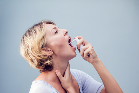 Spray for sore throat. Photo of a woman who treats her throat with a spray and sprinkles it in her mouth. The concept of health and disease.
