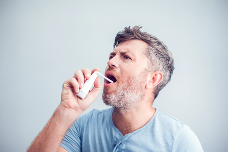 Spray for sore throat. Photo of a man who treats his throat with a spray and sprinkles it in his mouth. The concept of health and disease.