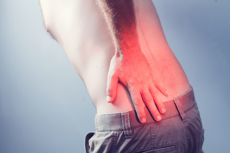Lumbago symptom. Young man holding his painful inflamed loin. Health care and medicine. Stock Photo