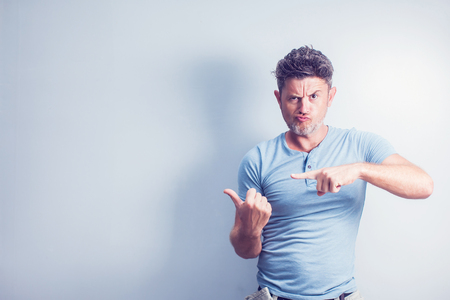 Middle age man smiling broadly showing thumbs up gesture to camera, expression of like and approval isolated over blue background
