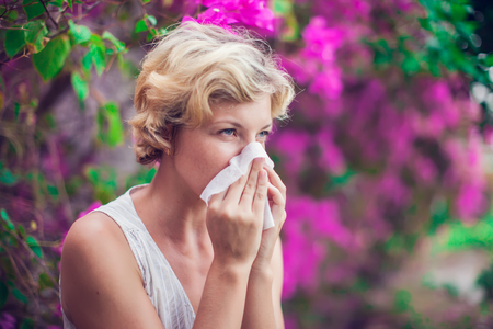 Woman with allergy symptom blowing nose Stock fotó