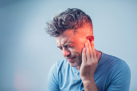 male having ear pain touching his painful head isolated on gray background