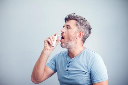 Spray gegen Halsschmerzen. Foto eines Mannes, der seinen Hals mit einem Spray behandelt und in seinen Mund streut. Das Konzept von Gesundheit und Krankheit.