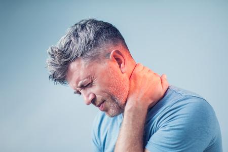 Jonge man die aan nekpijn lijdt. Hoofdpijn pijn. Stockfoto
