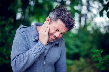 Unhappy male having ear pain touching his painful head outdoor