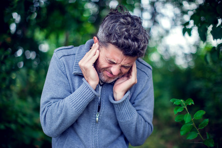 Unhapy male having ear pain touching his painful head outdoor Stock Photo
