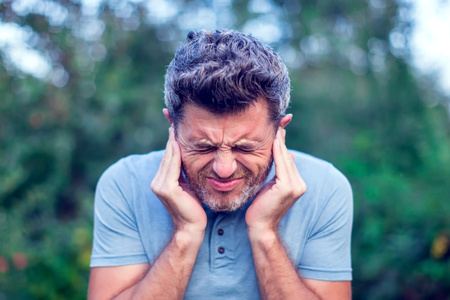 Unhappy man having ear pain touching his painful head outdoor Stock Photo