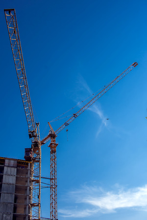 Construction crane on a building site against blue sky background. Stock Photo