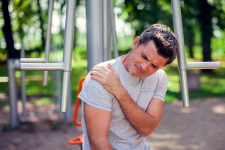 Au unhappy man feeling pain in his shoulder during sport and workout in the park. Sport, medicine and people concept