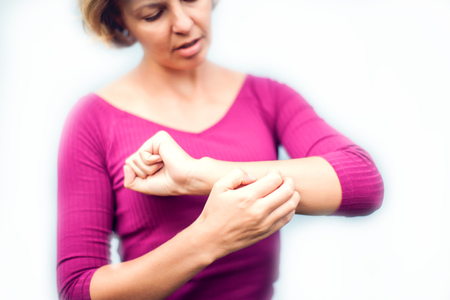 People, healthcare, dermatology, allergy and health problem concept - unhappy woman suffering from hand inch isolated on white background Stock Photo