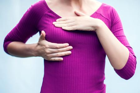 Close-up bijgesneden portret jonge vrouw met pijn aanraken borst geïsoleerd op een witte achtergrond
