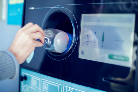 Shoppers return their bottles and cans of reusable packagings in a reverse vending machine. 版權商用圖片
