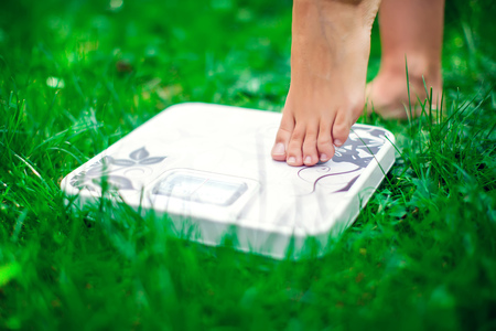 Lose weight concept. A person on a scale on a grass measuring kilograms outdoor
