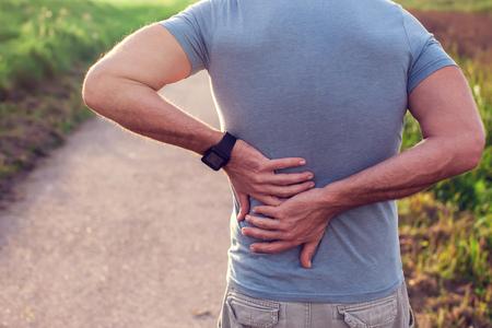 Persone, assistenza sanitaria e concetto di problema: un uomo che soffre di dolori alla schiena o redini all'aperto