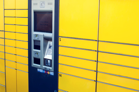 Self-service terminal for parcel post with yellow facade. Concept: delivery, self, easy.
