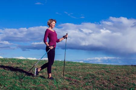 Nordic Walking, Bewegung, Sport, Abenteuer, Wanderkonzept - eine Frau, die in der Natur wandert