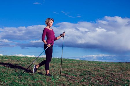 Nordic walking, exercise, sport, adventure, hiking concept -a woman hiking in the nature Фото со стока