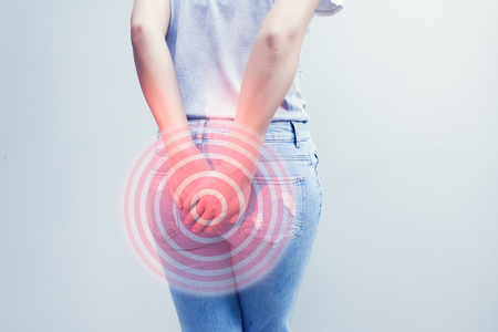 Woman hand holding her bottom because having Abdominal pain and Hemorrhoids, Health care concept. Stockfoto