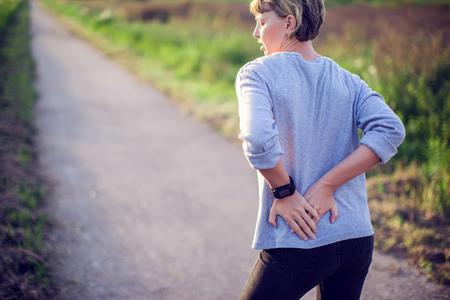 Concepto de personas, salud y problemas: mujer que sufre de dolor en la espalda o riendas al aire libre