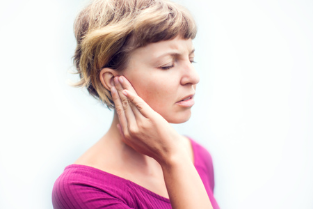 Tinnitus. Unhappy female having ear pain touching her painful head isolated on white background 스톡 콘텐츠