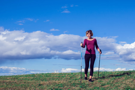 Nordic walking, exercise, sport, adventure, hiking concept -a woman hiking in the nature