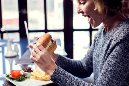 Happy woman is eating burger and smiling while spending time in cafe