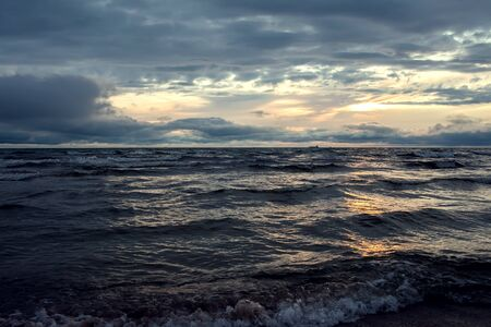 A sunset on the beach in summer. Sea and eveninig sky with clouds