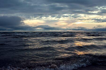 Een zonsondergang op het strand in de zomer. Zee en avondlucht met wolken