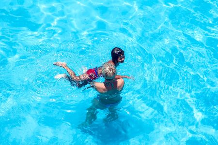 Mother teaches her sun swim in the pool. Family and activity concept