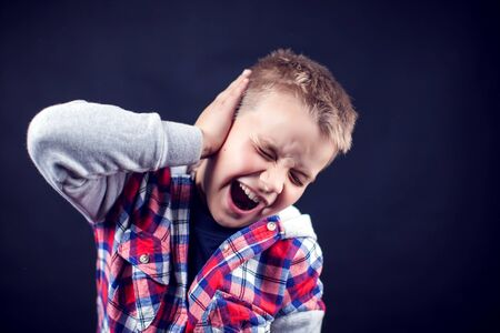 A boy feels strong ear pain. Children, healthcare and medicine concept Banque d'images - 131703108