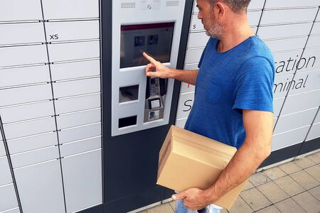 Man client using automated self service post terminal machine or locker to deposit a parcel for storage Archivio Fotografico - 131828598